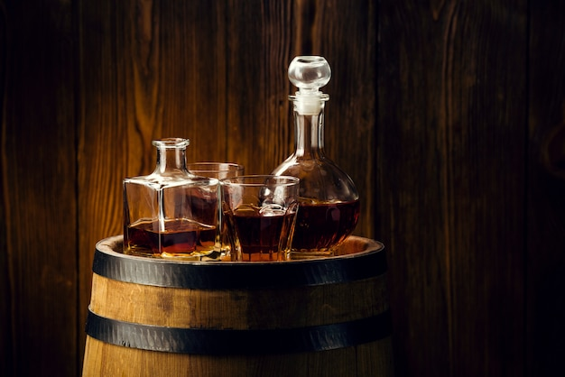 Brandy and brandy in decanters stand on an oak barrel, strong alcoholic drinks in the basement
