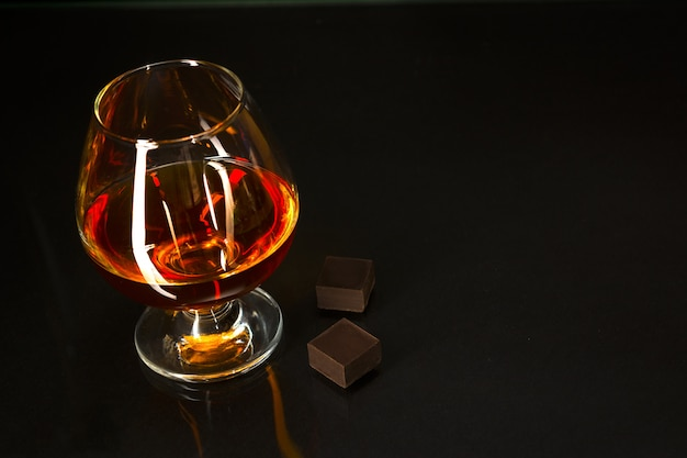 Brandy glass and chocolate on black background