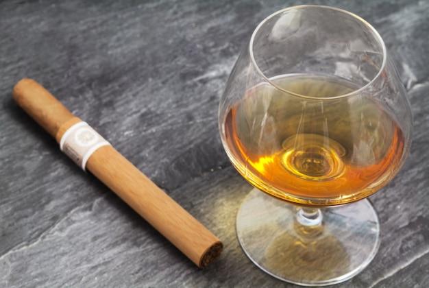 Brandy glass and cigar over ardesia