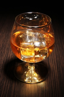 Brandy glass with ice on wooden surface