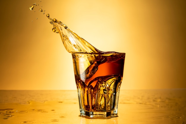 Brandy in a glass with splash on a background of yellow background with reflection, alcoholic beverages