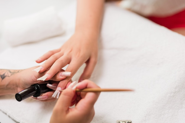 브라질 라틴 여성 매니큐어 전문가가 고객의 섬유질 손톱에 가을을 연상케합니다.