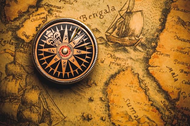 오래 된 갈색 지도에 황동 골동품 나침반