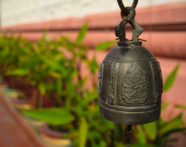 Brass bell on blur the wall and green plants background