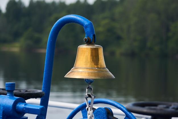 船の前甲板にある真ちゅう製の鐘、ぼやけた樹木が茂った海岸を背景にクローズアップ