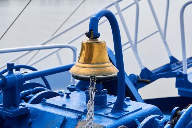 曇った光の中で船の前甲板に真鍮の鐘、クローズアップ