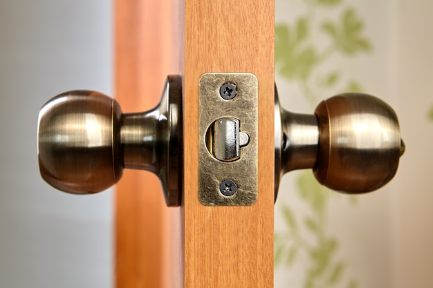 Brass door knob with latch and lock.
