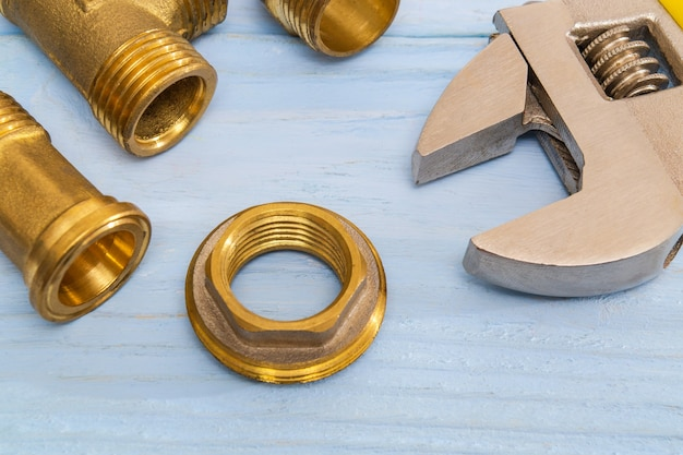 Brass fittings and adjustable wrench on blue boards