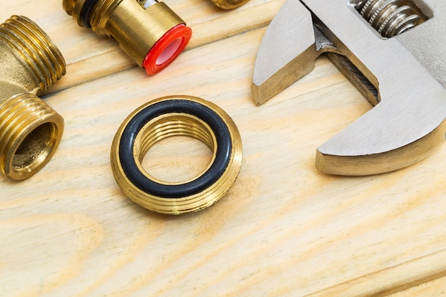 Brass fittings and adjustable wrench on wooden boards