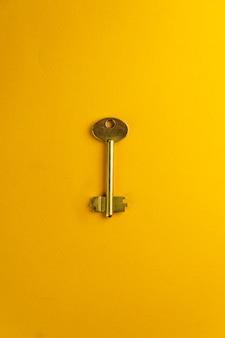 Brass key on yellow background