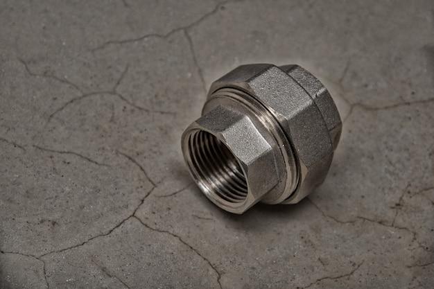 真ちゅう製の還元カップリング。濃い灰色のセメントの背景、クローズアップ、コピースペースにフィッティングの雌ねじパイプ。パイプの接続。リノベーションコンセプト