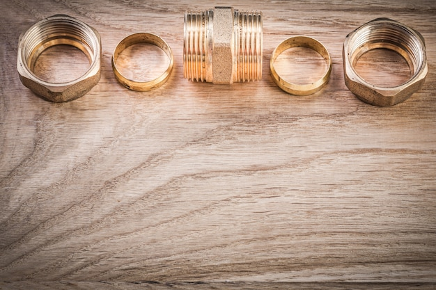 Brass threaded nipple hose connectors on wooden board plumbing concept
