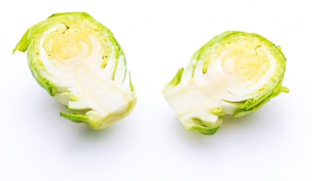 Крупный план сырой свежей брюссельской капусты, разрезанной на две половинки (капуста - brassica oleracea). изолированные на белом фоне
