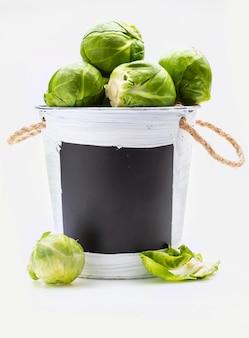 Чаша с сырой, свежей, цельной и нарезанной брюссельской капустой (капуста - brassica oleracea). копировать пространство изолированные на белом