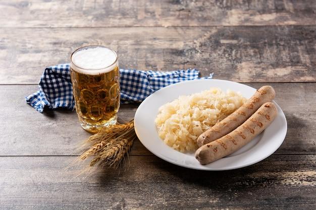 브라트부어스트 소시지, 소금에 절인 양배추, 프레첼, 맥주를 나무 테이블에
