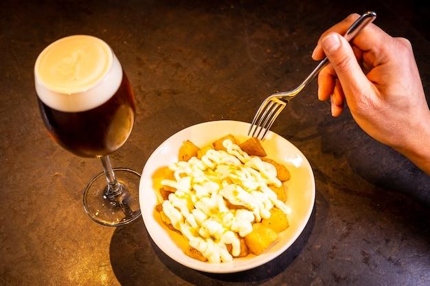 파란색 접시에 검은 배경에 맥주와 함께 아이올리 소스를 곁들인 브라바스