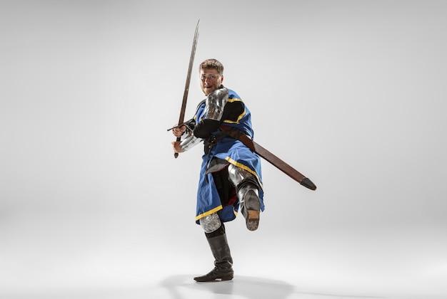 Храбрый бронированный рыцарь с профессиональным боевым оружием, изолированные на белом фоне студии. историческая реконструкция родной битвы воинов. понятие истории, хобби, античного военного искусства.