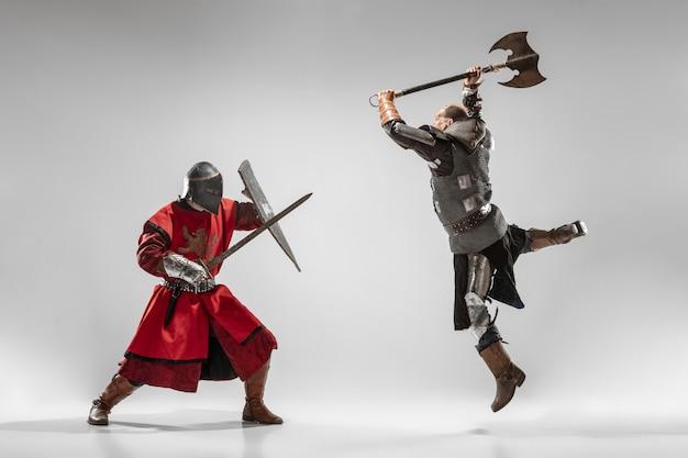 白いスタジオの背景に分離されたプロの武器の戦いを持つ勇敢な装甲騎士。戦士のネイティブの戦いの歴史的な再構築。歴史、趣味、アンティークの軍事芸術の概念。