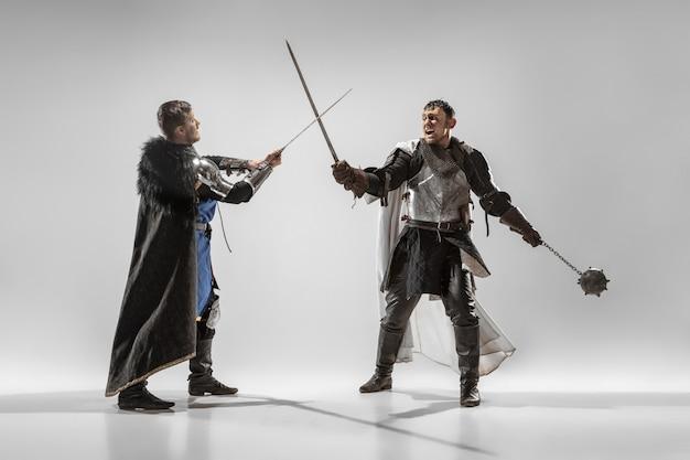 白いスタジオの背景に分離されたプロの武器の戦いを持つ勇敢な装甲騎士。