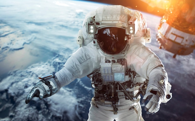 Отважный космонавт выходит в открытый космос на околоземной орбите. люди в космосе. элементы этого изображения, предоставленные наса