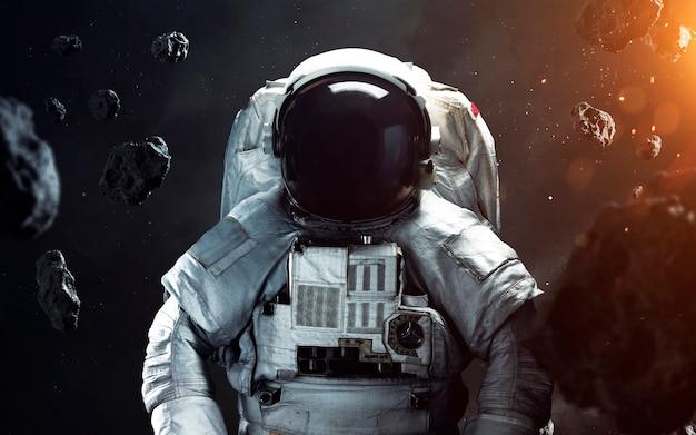 Отважный космонавт на выходе в открытый космос. люди в космосе. элементы этого изображения, предоставленные наса