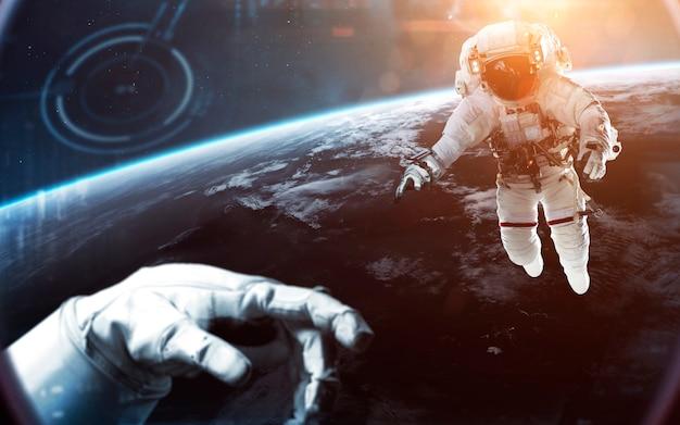 Отважные космонавты смотрят на красивую голубую землю. люди в космосе. элементы этого изображения, предоставленные наса