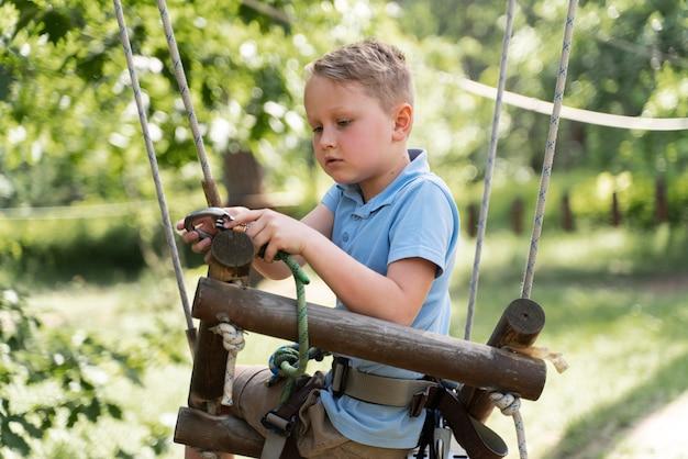 Ragazzo coraggioso che si diverte in un parco avventura