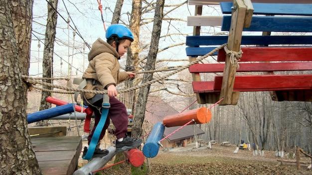 Храбрый мальчик в шлеме поднимается по лестнице на веревочных курсах