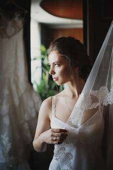 Храбрая невеста в нижнем белье прячется за завесой, стоящей в комнате