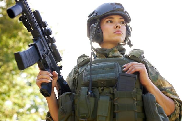 勇敢な白人女性は、軍のスーツを着て、武器の銃やライフルの狩猟に従事しています