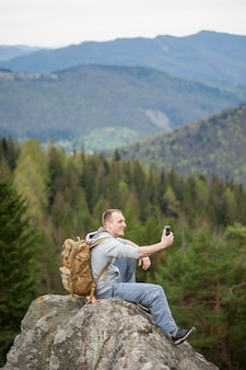 Brave climber with a backpack sitting on the top of a rock and makes selfie on the his phone