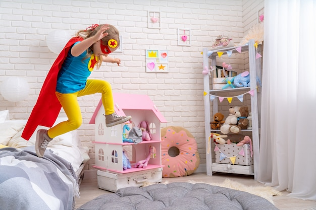 Brave cute little girl jumps out of bed, imagining flight.