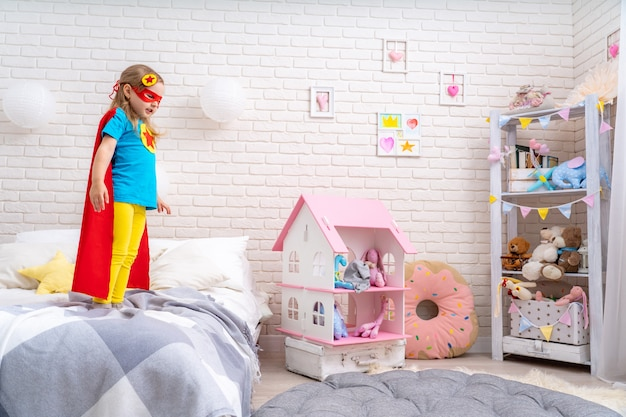 Brave cute little girl wants to jump out of bed, imagining flight.