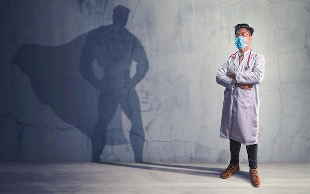 벽에 슈퍼 히어로의 그의 그림자와 함께 용감한 의사. 강력한 남자의 개념