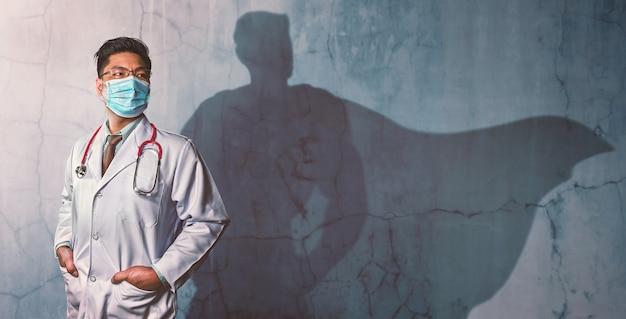 壁にスーパーヒーローの影を持った勇敢な医者。強力な男の概念