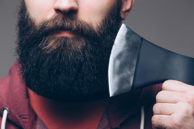 勇気。残忍な木こり。木を切る。鋭い刃。残忍さと男らしさ。あごひげを生やした木こり。木こりスタイル。斧を持つ男。ひげを生やした男は白で隔離された斧を保持します。危険の概念。