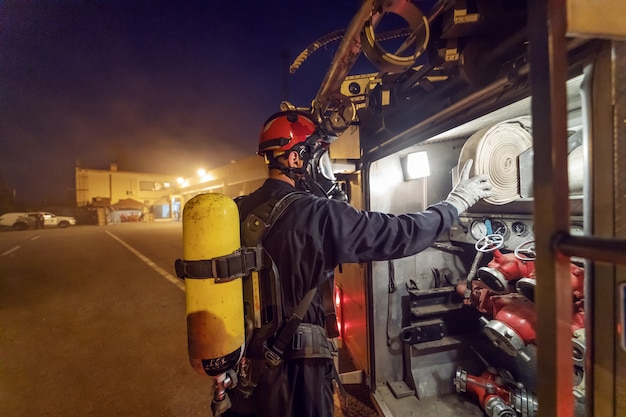 夜に火を消すために消防車からホースを取る勇敢な消防士。