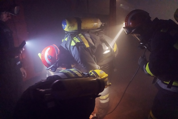 불타는 차에서 남자를 풀어주는 용감한 소방관.
