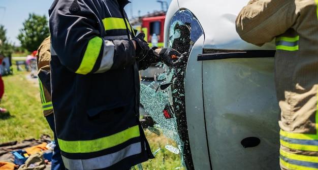 車の窓を壊し、自動車事故の犠牲者を救おうとしている勇敢な消防士。