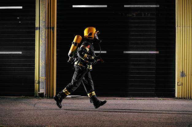 Отважный пожарный в защитной форме со всем снаряжением бежит к тушению пожара.