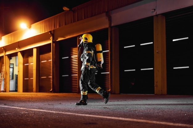 Brave fireman in protective uniform with full equipment running to taking care of fire.