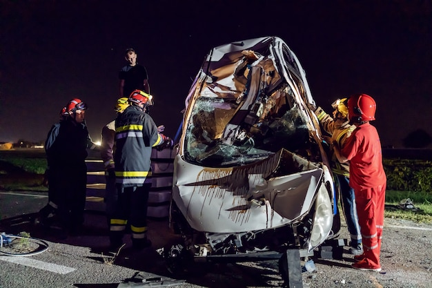 Brave firemen trying to release man from crashed car.