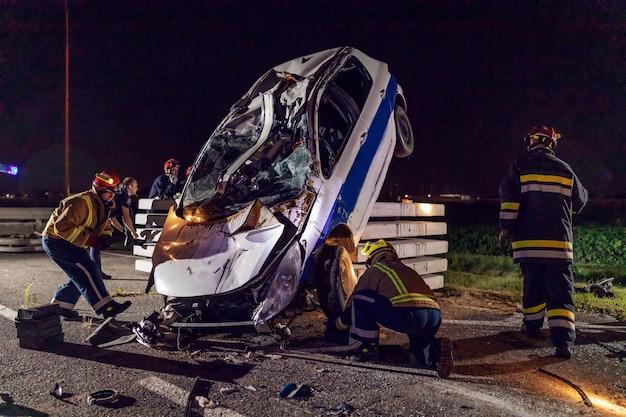 墜落した車から人を解放しようとしている勇敢な消防士。