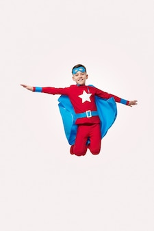 スーパーヒーローの衣装でジャンプする勇敢な子供
