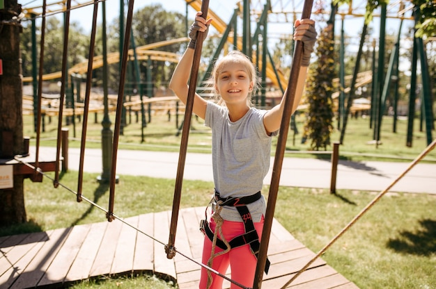 Brave kids in equipment climbs in rope park, playground. children climbing on suspension bridge, extreme sport adventure on vacations, entertainment outdoors