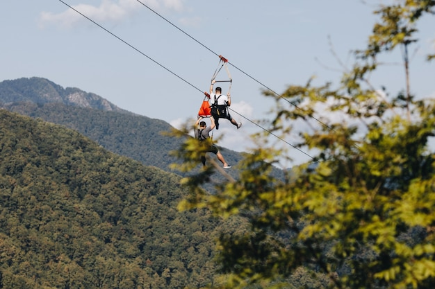 A brave man descends on a zip line high in the mountains above the forest.