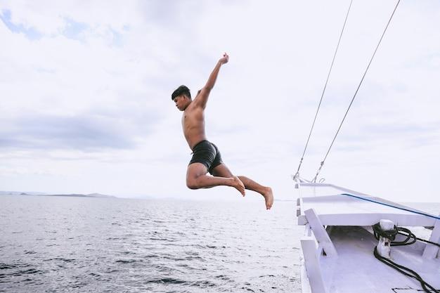 Храбрый человек прыгает в море с лодки