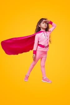 距離を見ている勇敢なスーパーヒーローの子供の女の子