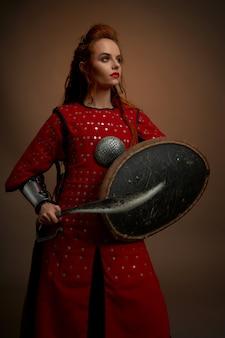Храбрая женщина в средневековой тунике позирует с оружием.
