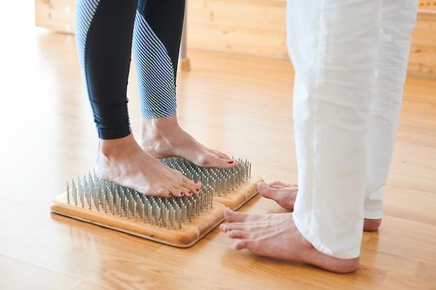 Храбрая женщина, стоя на ложе из ногтей на практике йоги